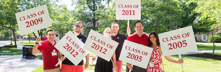 Alumni holding class year signs at Alumni Weekend parade party